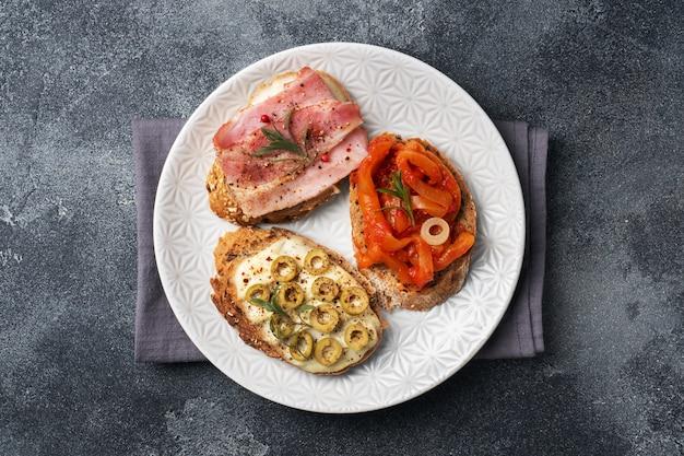 Sandwichs au pain complet avec du fromage à la crème, du bacon et des olives, des poivrons en conserve avec de la tomate dans une assiette.