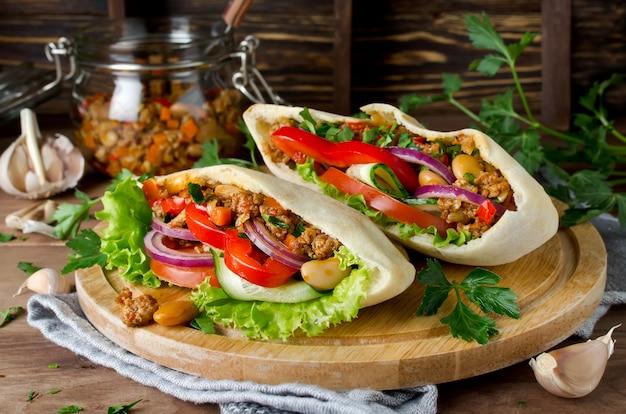 Sandwichs au pain pita avec viande, haricots et légumes
