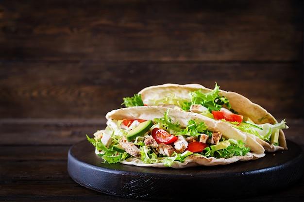 Sandwichs au pain pita avec viande de poulet grillée, avocat, tomate, concombre et laitue servis sur fond de bois.