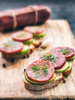 Sandwichs au pain de seigle et salami de saucisse fumée à l'aneth et au concombre sur planche de bois à découper, gros plan