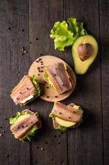 Sandwichs au poisson fumé sur une planche sur fond sombre