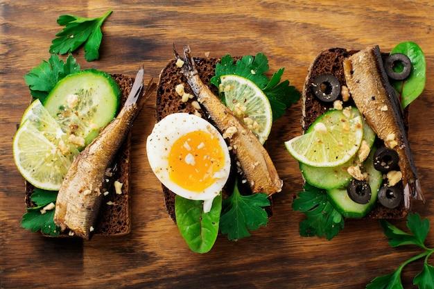 Sandwichs au poisson avec sprats, concombre, citron vert, œufs durs, feuilles de persil et mangue sur pain de seigle sur un vieux béton gris. mise au point sélective