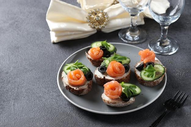 Sandwichs au saumon, concombre, fromage à la crème et olives noires sur fond gris. collation de vacances. espace de copie