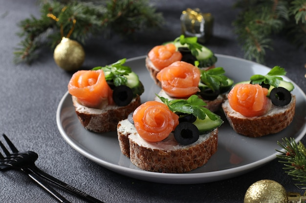 Sandwichs au saumon, concombre, fromage à la crème et olives noires sur fond gris. collation de vacances maison.