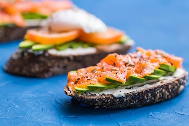 Sandwichs au saumon fumé, œufs, sauce et avocat sur fond bleu. concept de petit-déjeuner et