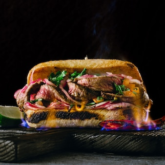 Sandwichs au steak épicé grillé steak dans une flamme de feu sur des planches à découper en bois sur fond sombre se bouchent