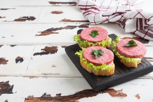 Sandwichs aux feuilles de laitue et saucisses de salami tranchées sur une planche à découper en bois