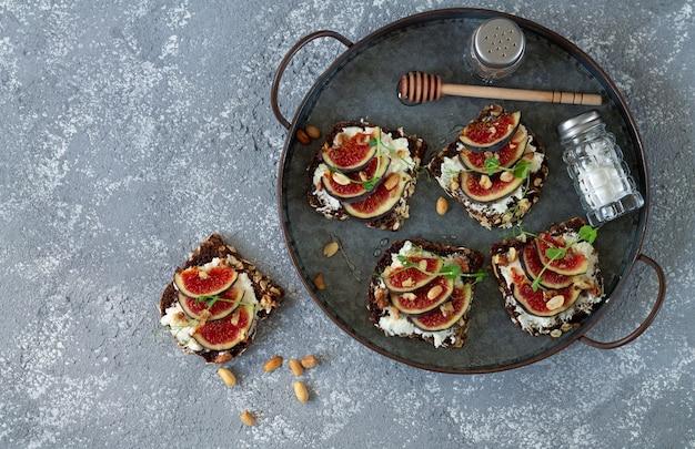Sandwichs aux figues avec du mascarpone, du miel et des noix sur le plateau de vue de dessus