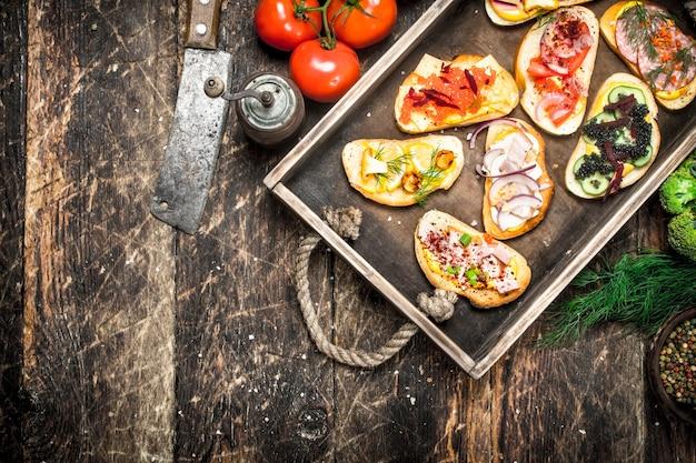 Sandwichs aux fruits de mer, salami, légumes frais baconnd sur table en bois.