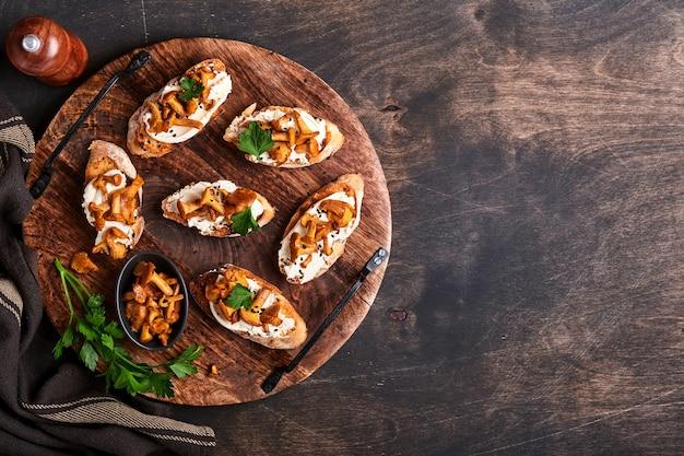 Sandwichs aux girolles au fromage. sandwich ouvert avec fromage crémeux, assaisonnements et poivre et persil frais sur un vieux fond en bois. maquette. vue de dessus.