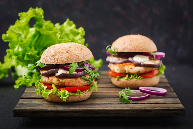 Sandwichs aux hamburgers de poulet épicés juteux avec tomate et aubergine