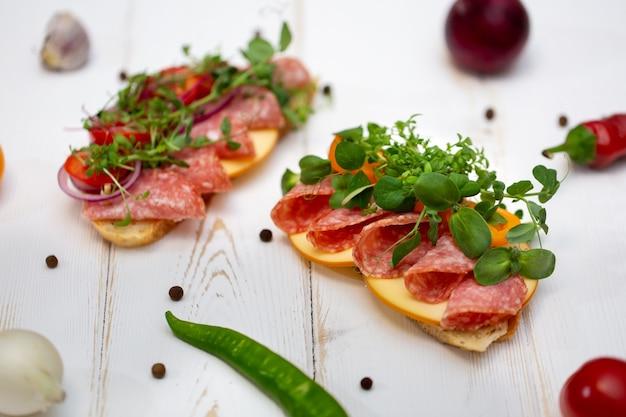 Sandwichs aux saucisses, fromage et micro-verts sur fond blanc