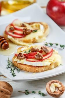 Sandwichs à la bruschetta au brie ou au camembert, pommes, noix de grenoble, thym et miel