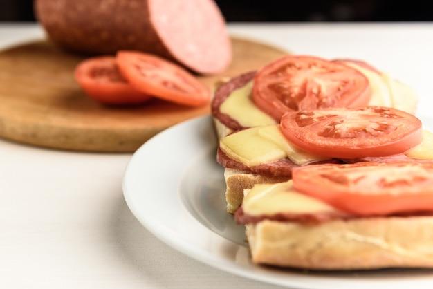 Sandwichs chauds avec saucisse au fromage fondu, salami et tomates