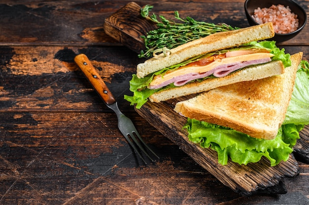 Sandwichs club jambon de dinde avec fromage, tomates et laitue sur une planche à découper en bois