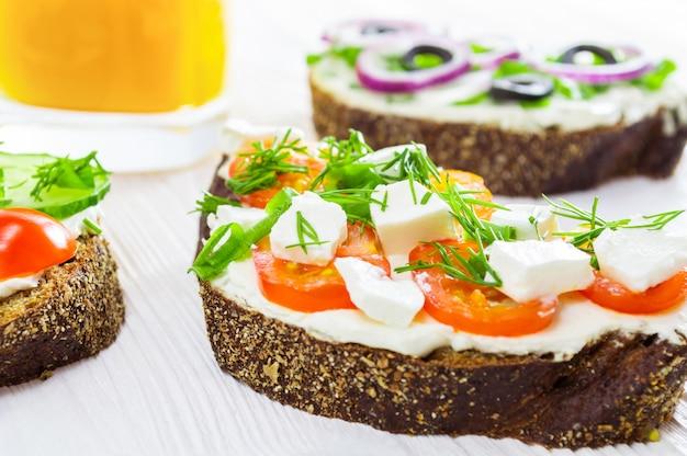 Sandwichs avec du fromage à la crème et des légumes et un verre de jus d'orange.