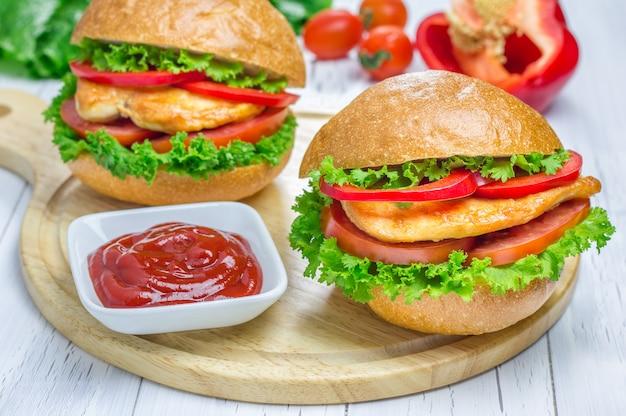 Sandwichs avec filet de poulet rôti, tomate et paprika sur planche de bois