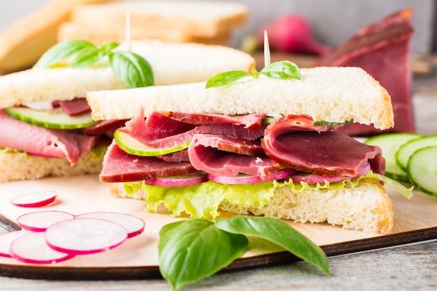 Sandwichs frais au pastrami, concombre, radis et basilic sur une planche à découper. snack américain. style rustique. fermer