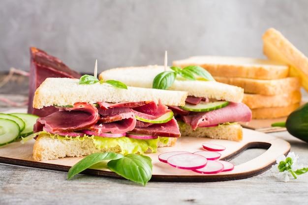 Sandwichs frais au pastrami, concombre et radis sur une planche à découper. snack américain. style rustique.