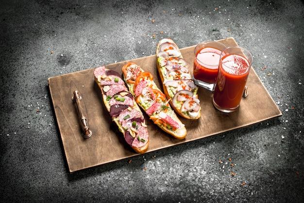 Sandwichs frais avec du jus de tomate sur l'ancien plateau sur table rustique.