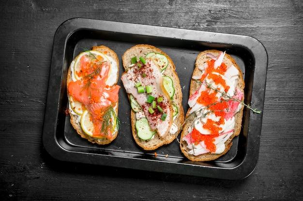 Sandwichs frais de fruits de mer avec saumon, caviar, bacon et légumes.
