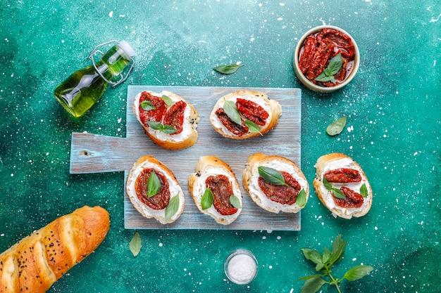 Sandwichs italiens - bruschetta au fromage, tomates séchées et basilic.