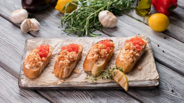Sandwichs et morceau de citron. tomates hachées et chair de poisson. bruschetta au saumon. délicieux apéritif italien.