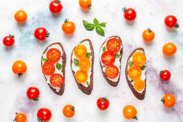 Sandwichs ouverts avec fromage cottage, tomates cerises et basilic.