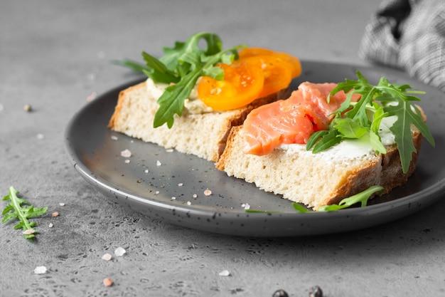 Sandwichs ouverts avec pain de blé et de seigle, tomates, saumon fumé et roquette