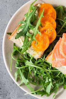 Sandwichs ouverts sains avec du pain artisanal avec du fromage à la crème, du saumon, des tomates et de la roquette