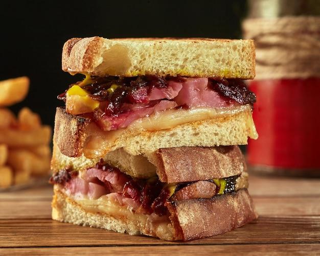 Sandwichs de pain grillé avec jambon frit bacon oignon caramélisé et sauce hollandaise