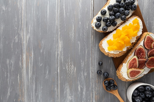 Sandwichs à plat avec fromage à la crème et fruits avec copie-espace