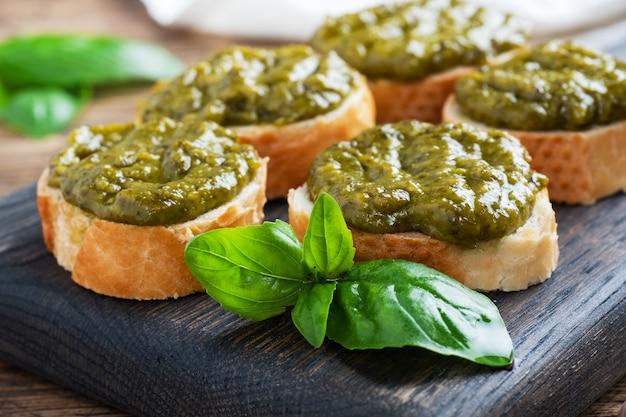 Sandwichs avec sauce pesto, feuilles de basilic frais et ail. une délicieuse collation saine. fond rustique en bois. fermer