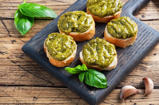 Sandwichs avec sauce pesto, feuilles de basilic frais et ail. une délicieuse collation saine. fond rustique en bois.