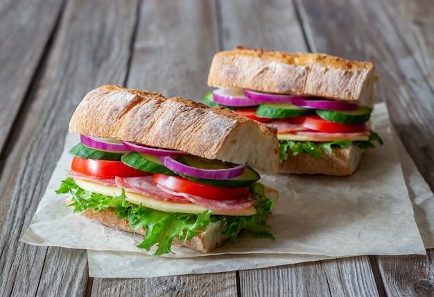 Sandwichs avec saucisse, fromage et salade verte