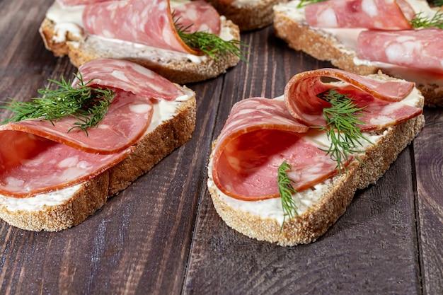Sandwichs à la saucisse fumée et au fromage à la crème. décoré avec des herbes à l'aneth. sur un fond en bois sombre. copiez l'espace.