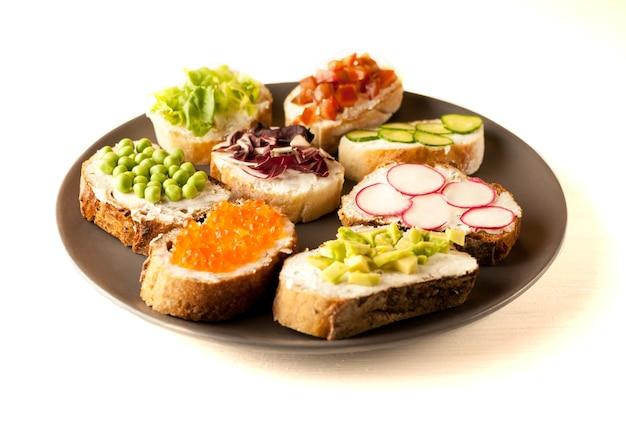 Sandwichs ou tapas préparés avec du pain et des ingrédients savoureux. cela pourrait être une bonne nourriture pour un petit-déjeuner sain ou un déjeuner. copiez l'espace pour votre texte