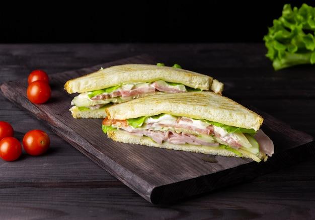 Sandwichs triangulaires avec pain grillé, laitue et légumes sur fond sombre. petit-déjeuner ou déjeuner sain et délicieux.