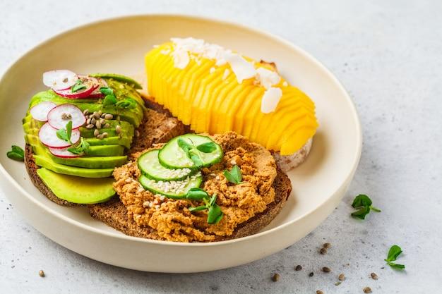 Sandwichs végétaliens à la mangue, avocat et pâté de tofu sur une assiette blanche.