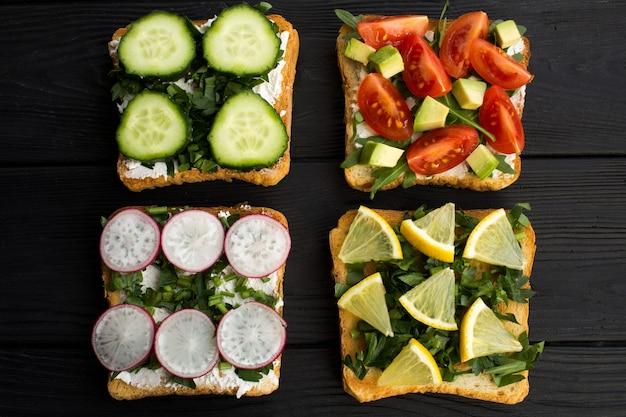Sandwichs végétariens aux légumes et fruits sur le fond en bois noir.vue de dessus.