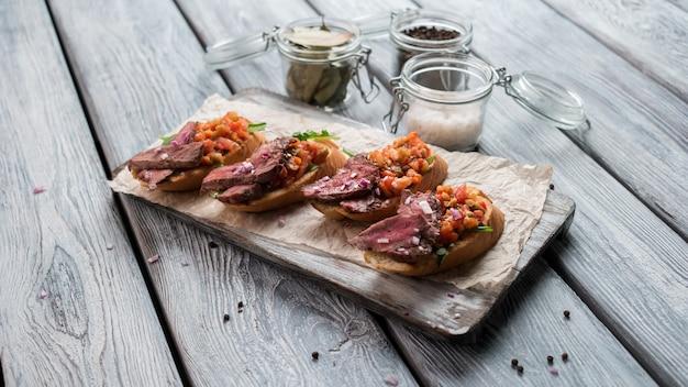 Sandwichs à la viande et aux herbes. surface en bois gris. repas de la cuisine italienne. snack et épices.