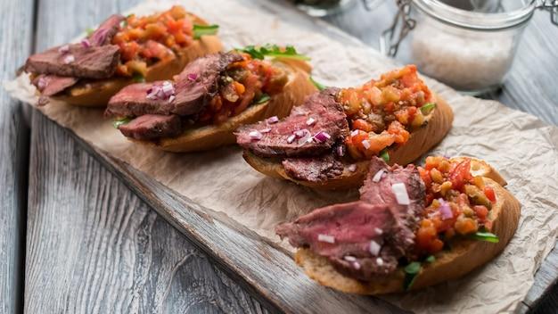 Sandwichs à la viande cuite. mélange de légumes hachés. délicieuse bruschetta au veau. snack salé sur planche de bois.