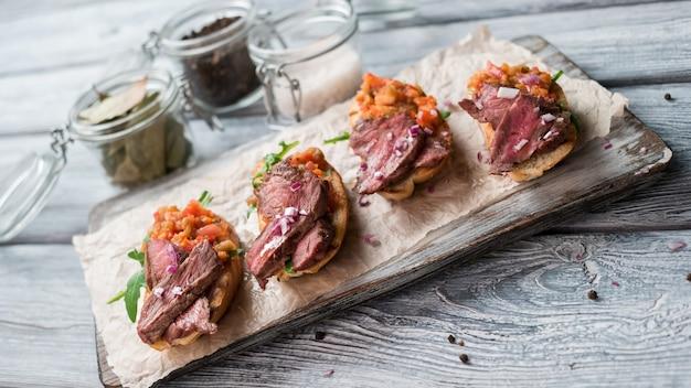 Sandwichs à la viande. mélange de légumes cuits. oignon haché sur bruschetta. veau juteux et roquette fraîche.