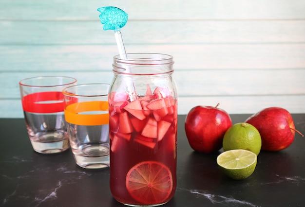 Sangria au vin rouge fait maison avec une paire de verres et d'ingrédients sur la table