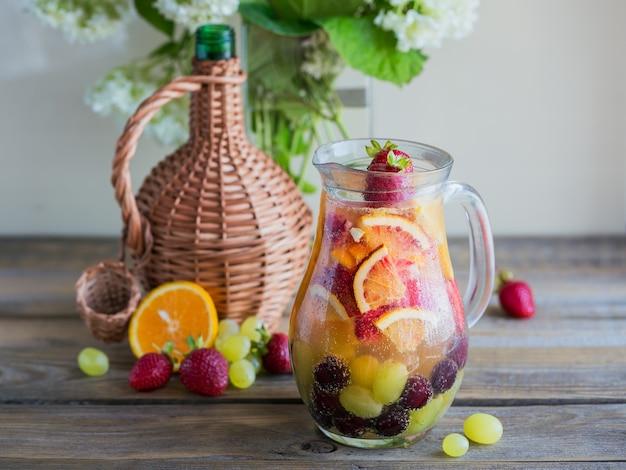 Sangria aux fruits rafraîchissante maison ou punch avec champagne, fraises, oranges et raisins