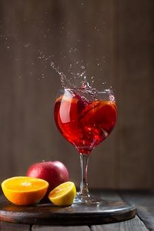 Sangria en verre avec éclaboussures et ingrédients - orange, citron et pomme, fond en bois foncé