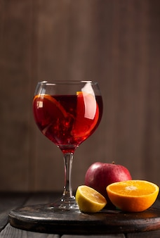 Sangria en verre avec des ingrédients - orange, citron et pomme, fond en bois foncé