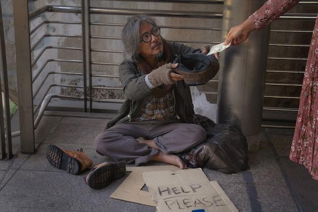 Un sans-abri est assis sur une passerelle en ville. il tient un chapeau et reçoit un dollar.