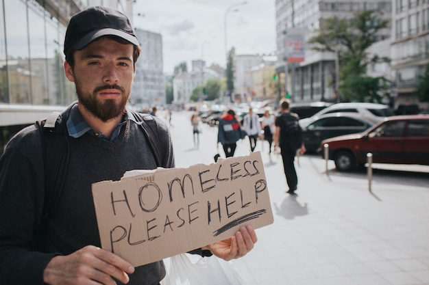 Sans-abri est debout dans la rue et montre le panneau qui dit sans-abri s'il vous plaît aider