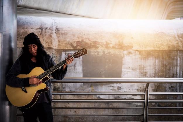 Sans-abri, levez-vous, guitare, chanter pour des dons.